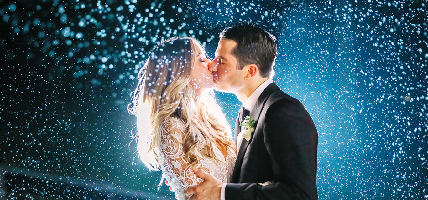 bride and groom kissing in snowy weather