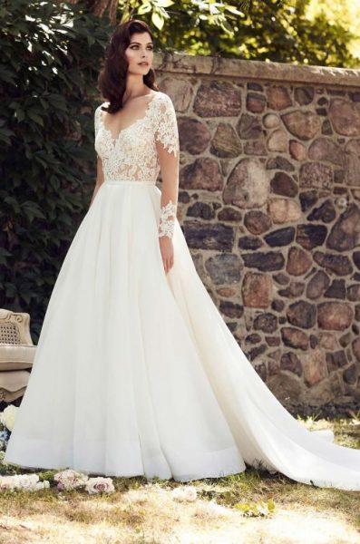 bride in Paloma Blanca dress next to brick wall