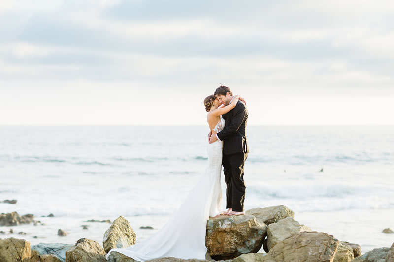 kristen and chase hugging on rocks by the beach