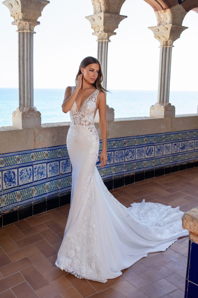Sleeveless v-neckline lace embroidered crepe sheath wedding dress with sheer bodice by Pronovias x Kleinfeld - Image 1